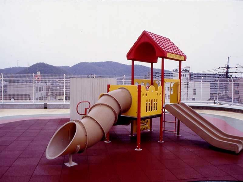 Beispielinstallation von roten Fallschutzplatten auf einem Kinder-Spielplatz